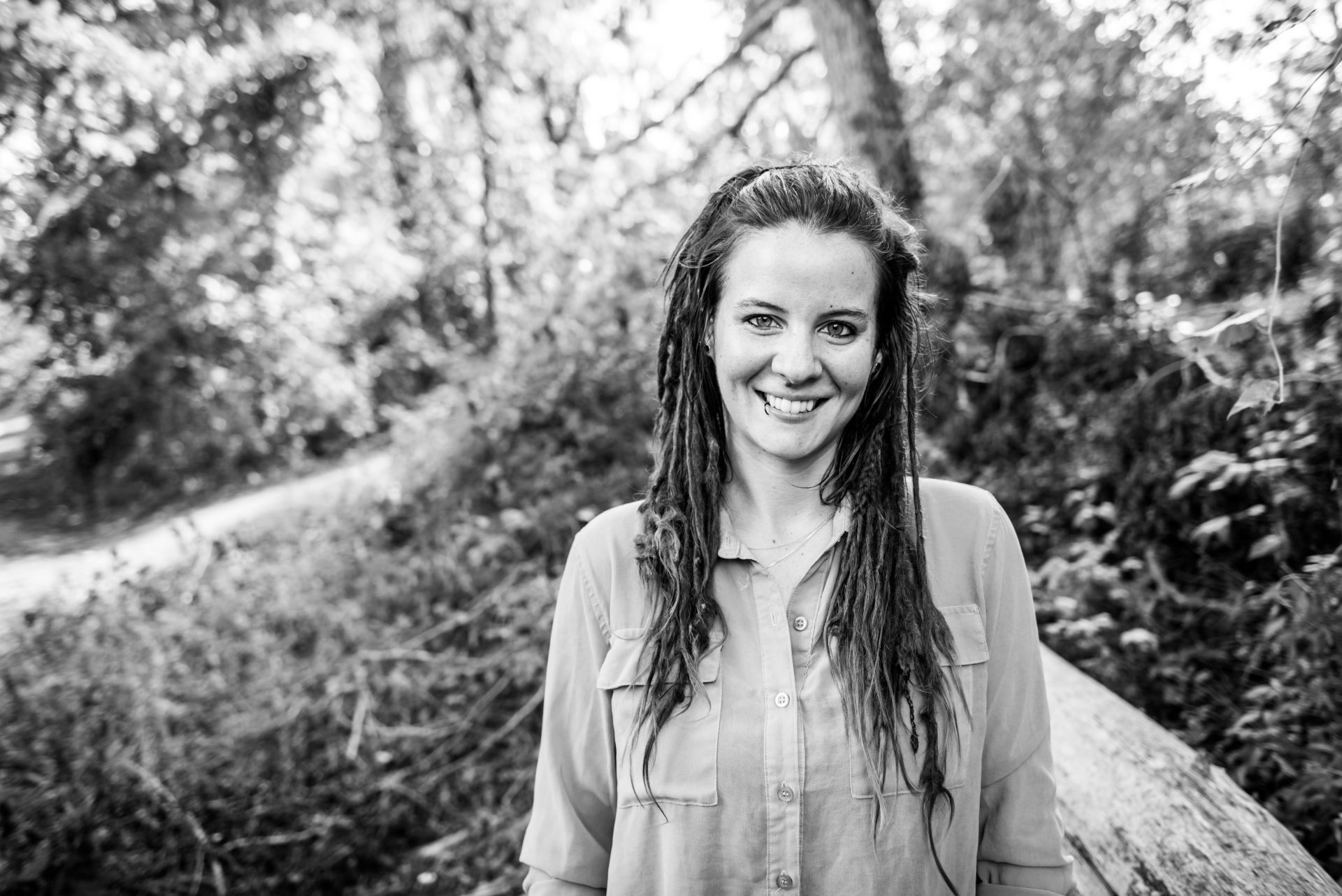 Black & white photo of Rachel, a white woman with dark dreadlocks wearing a button-down top, standing outdoors.